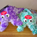 One purple and one turquoise soft toy starfish with large eyes