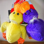 One yellow and one purple soft toy ducks both with white hair, an orange bill and orange feet with white pokkadots.